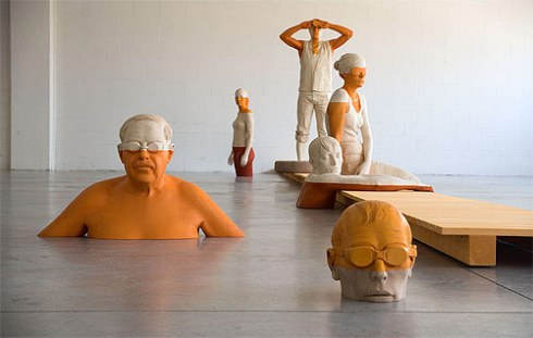 orange people in water sculpture by willy verginer